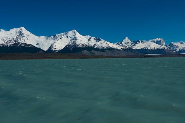 Snowy góry na brzegu jeziora argentino