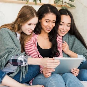 Snugging pod koc dziewczynami siedzi i patrzeje pastylka ekran