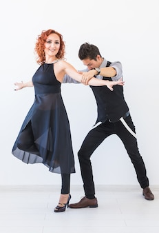 Social dance, bachata, kizomba, tango, salsa, people concept - młoda para tańczy nad białymi