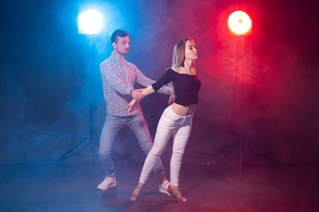 Social dance, kizomba, salsa and semba concept - młoda piękna para tańczy bachatę lub salsę w ciemności