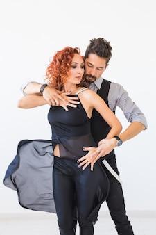 Social dance, salsa, zouk, tango, kizomba concept - piękna para tańczy bachatę na białym tle
