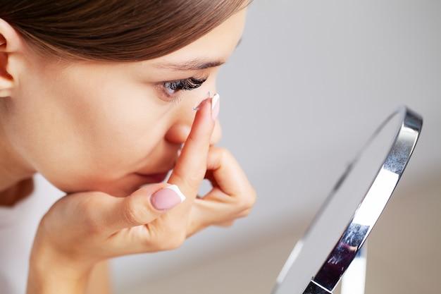 Soczewka kontaktowa do wizji. młoda kobieta zakłada w domu soczewki optyczne w pokoju