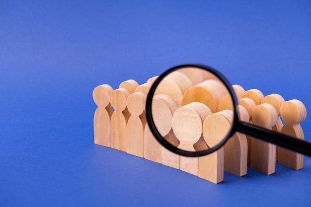 Soczewka lupa powiększająca poszukiwania szukając nowych kandydatów na drewniane figurki