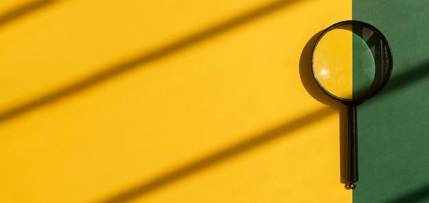 Soczewka powiększająca na jasnym słonecznym żółtym tle z pięknym banerem światła dziennego z miejscem na kopię