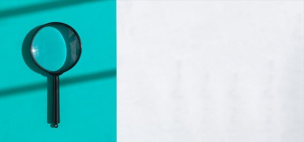 Soczewka powiększająca nad białym banerem z jasnoniebieskim paskiem koncepcji narzędzia wyszukiwania z miejscem na kopię