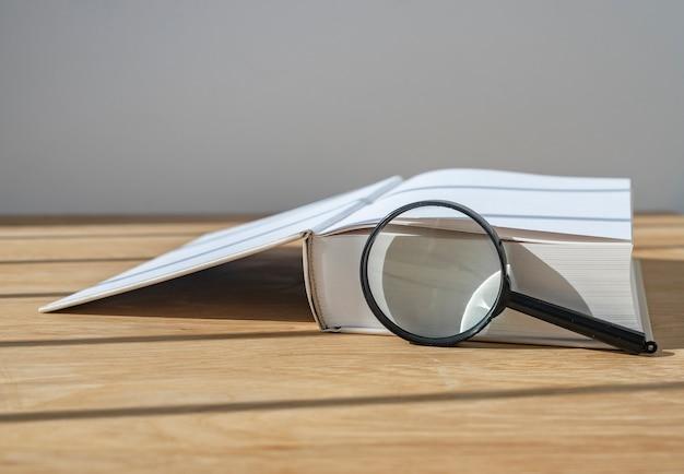 Soczewka powiększająca z otwartą grubą książką na drewnianym biurku ze światłem dziennym