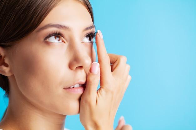 Soczewki kontaktowe do widzenia. młoda kobieta stosuje soczewki kontaktowe