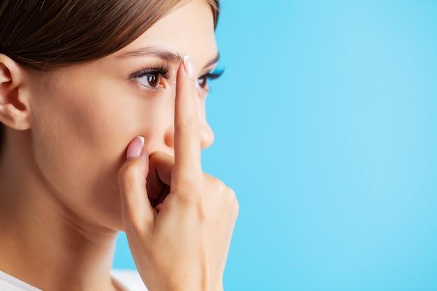 Soczewki kontaktowe do widzenia. zamyka up kobieta stosuje szkła kontaktowe