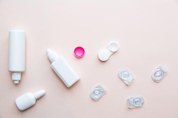 Soczewki kontaktowe i produkty do pielęgnacji soczewek na jasnoróżowym stole