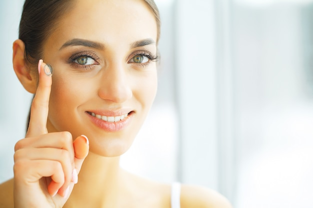 Soczewki kontaktowe vision. zbliżenie z piękną twarzy kobiety