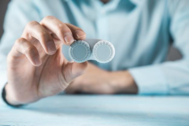 Soczewki optyczne ręka mężczyzny na niebieskim stole
