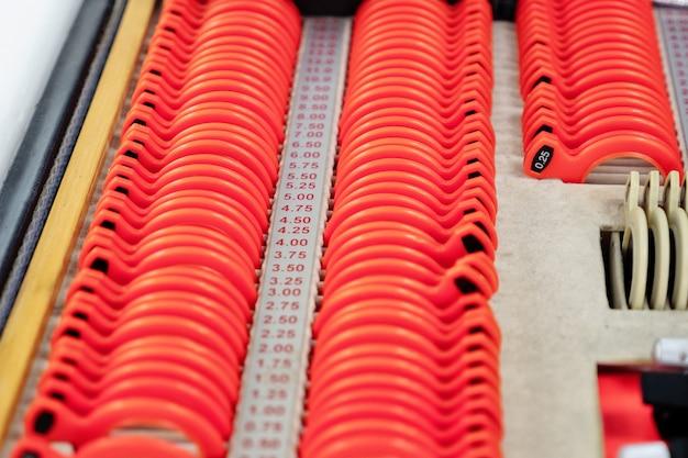 Soczewki optyczne z zestawu soczewek korekcyjnych wskazujące na płytkach kształt: wklęsły, wypukły, cylindryczny.