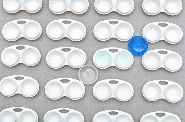 Soczewki w pojemniku na szarym tle. wzór pojemników na soczewki