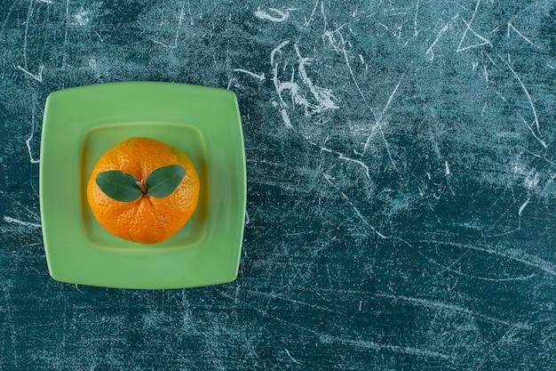 Soczysta mandarynka na podstawce, na marmurowym stole.
