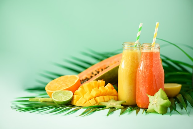 Soczysta papaja i ananas, mango, pomarańczowy koktajl owocowy w dwóch słoikach. detox, letnia dieta, koncepcja wegańska. świeży sok w szklanych butelkach