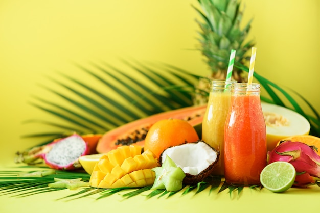Soczysta papaja i ananas, mango, pomarańczowy koktajl owocowy w dwóch słoikach. detox, letnia dieta, koncepcja wegańska.