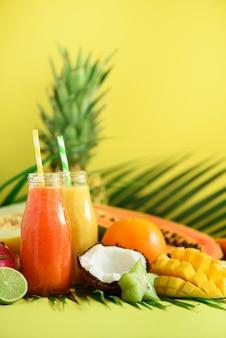 Soczysta papaja i ananas, mango, pomarańczowy koktajl owocowy w dwóch słoikach na żółtym tle. detox, letnia dieta, koncepcja wegańska.