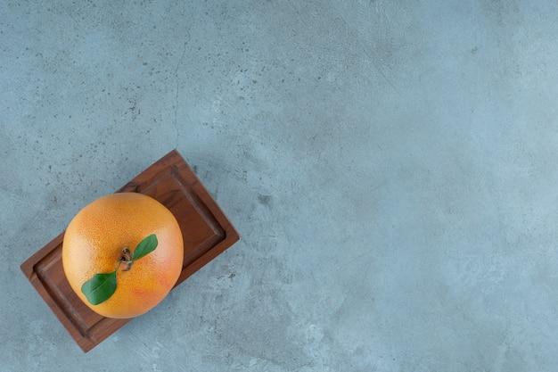 Soczysta pomarańcza na drewnianym talerzu, na marmurowym tle. zdjęcie wysokiej jakości
