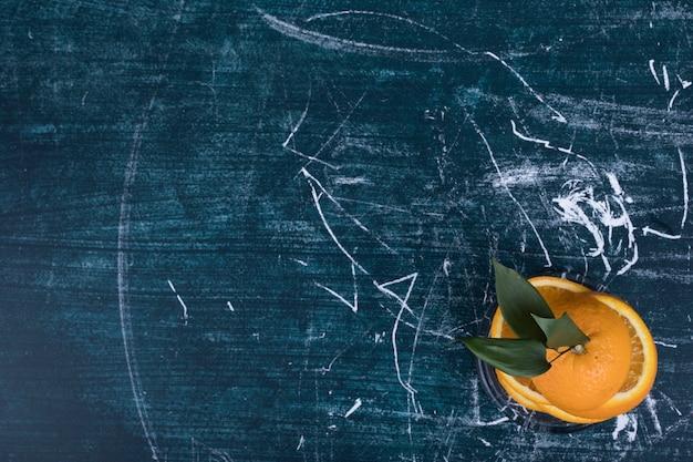 Soczysta pomarańcza w plasterkach z zielonymi liśćmi, widok z góry