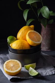 Soczyste cytryny i limonki w czarnej misce na szarym stole