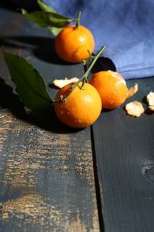 Soczyste dojrzałe mandarynki z liśćmi na drewnianym stole