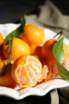 Soczyste dojrzałe mandarynki z liśćmi na obrusie