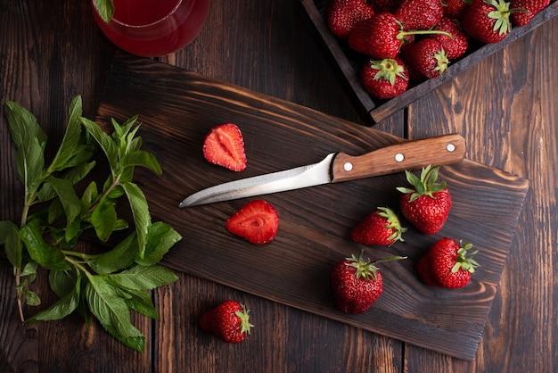 Soczyste dojrzałe truskawki na desce do krojenia z nożem na podłoże drewniane, styl rustykalny, zdrowa dieta surowa, z bliska.