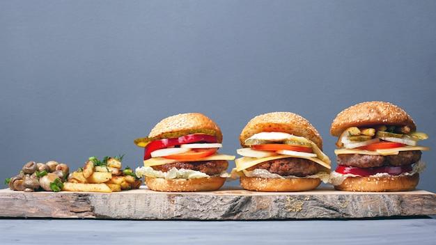 Soczyste hamburgery ze smażonymi ziemniakami i grzybami na drewnianym talerzu. hamburgery z serem kotletowym i warzywami na szarym tle.