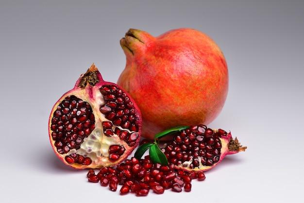 Soczyste i dojrzałe granaty na szarym tle owoce zawierają wiele witamin