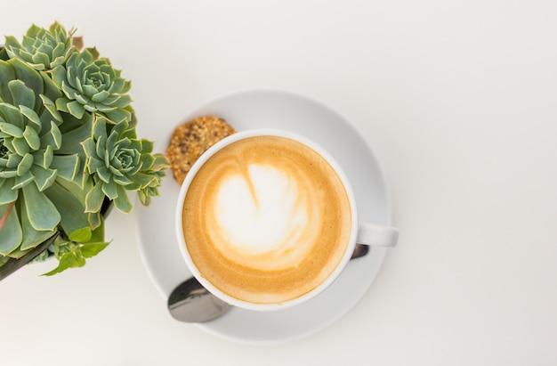 Soczyste i kawa latte na białym tle. kawa w białej filiżance z garnkiem, płasko świecki, kopia przestrzeń.