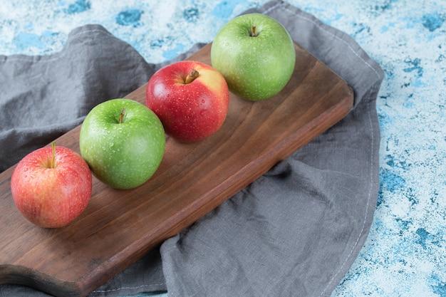 Soczyste jabłka na białym tle na drewnianym talerzu.