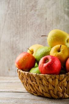 Soczyste jabłka w wiklinowym koszu na jasnym tle drewniane i grunge.