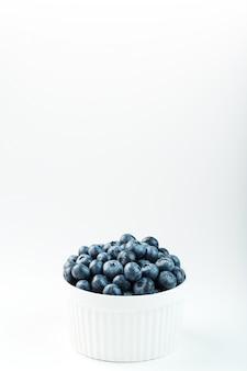 Soczyste jagody w białym pucharze na białym tle