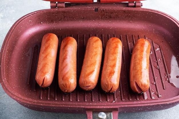 Soczyste kiełbaski pieczone na patelni grillowej. ścieśniać.