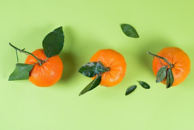 Soczyste letnie mandarynki z liśćmi na kolorowym zielonym tle