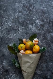Soczyste mandarynki z liśćmi i gałęziami jodły w papierowej torbie