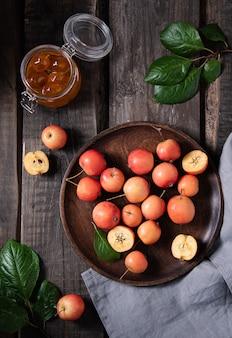 Soczyste mini jabłka w talerzu z słoikiem z dżemem na starym drewnianym