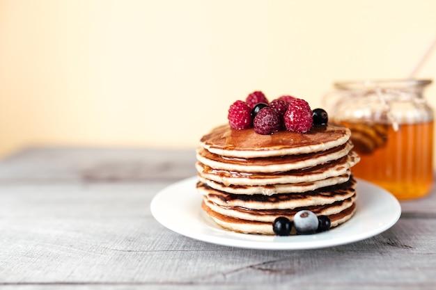 Soczyste naleśniki z jagodami i miodem na białym talerzu, łyżka, słoik, drewniany stół. wysokiej jakości zdjęcie