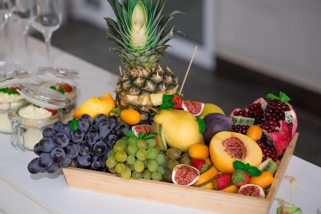 Soczyste owoce w drewnianym pudełku ananas winogrona mango figa brzoskwinia truskawka smoczy owoc