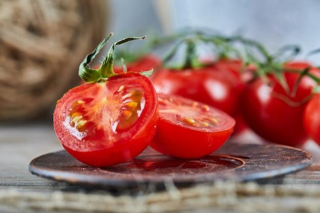 Soczyste plastry czerwonych pomidorów na talerzu ceramicznym.