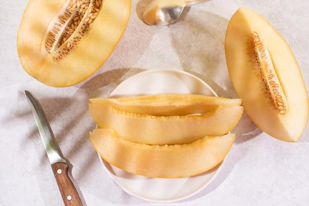 Soczyste plastry melona na talerzu z nożem na białym talerzu z pięknymi cieniami, letnie owoce.
