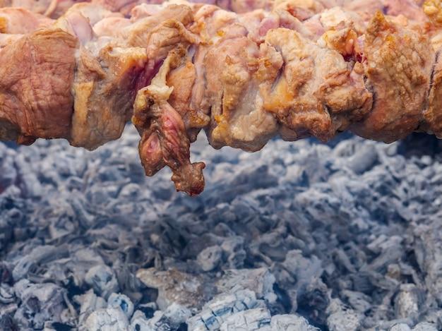 Soczyste plastry mięsa wieprzowego nawleczone na szaszłyki i grillowane na grillu węglowym