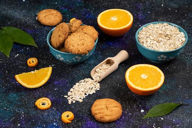 Soczyste pomarańcze z ciastkiem i płatkami owsianymi na ciemnym stole.