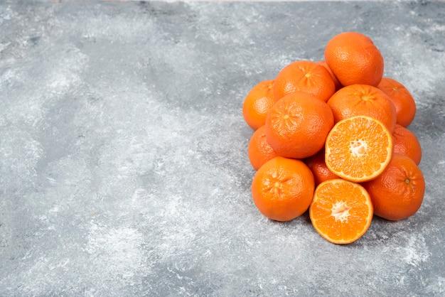 Soczyste pomarańczowe owoce z plastrami na kamiennym stole.
