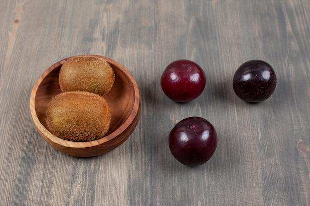 Soczyste śliwki z kiwi na drewnianym stole. wysokiej jakości zdjęcie