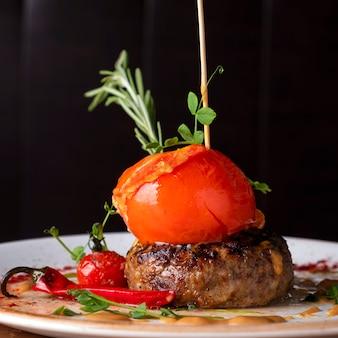 Soczyste smażone kotlety mięsne z pieczonymi pomidorami. zbliżenie