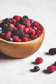 Soczyste świeże jagody, maliny i jeżyny w białej płytce na starej powierzchni drewnianych, selektywne focus