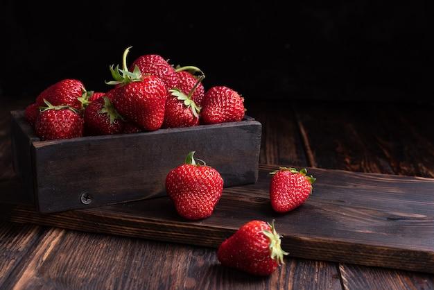 Soczyste świeże truskawki w drewnianym pudełku na drewnianym tle, letnie jagody, z bliska.