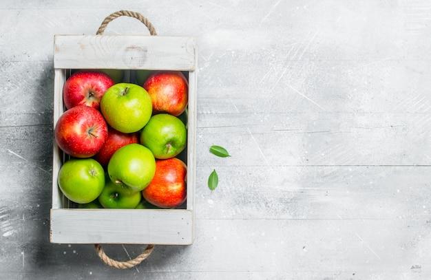 Soczyste, świeże zielone i czerwone jabłka w drewnianym pudełku.