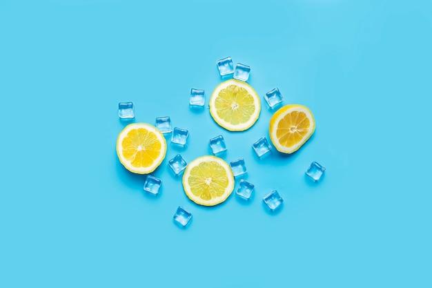 Soczyste świeże żółte plasterki cytryny i kostki lodu na niebiesko
